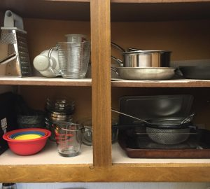 A ready to use cupboard, with a few small pans, bowls, measuring cups and hand chopper